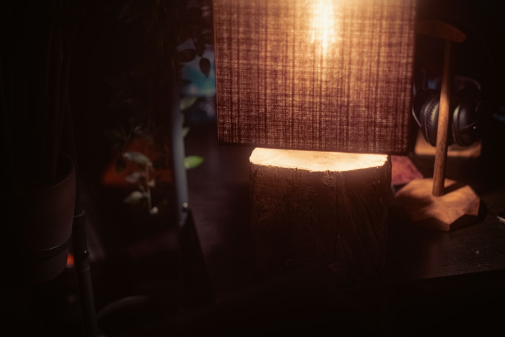 brown table lamp turned on near brown window curtain