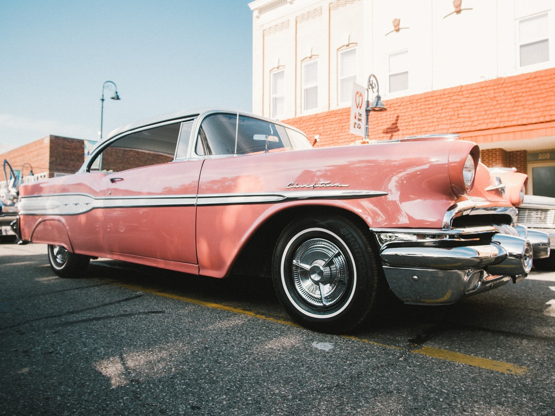 A Classic Pink Car Parked In the Street. - unsplash