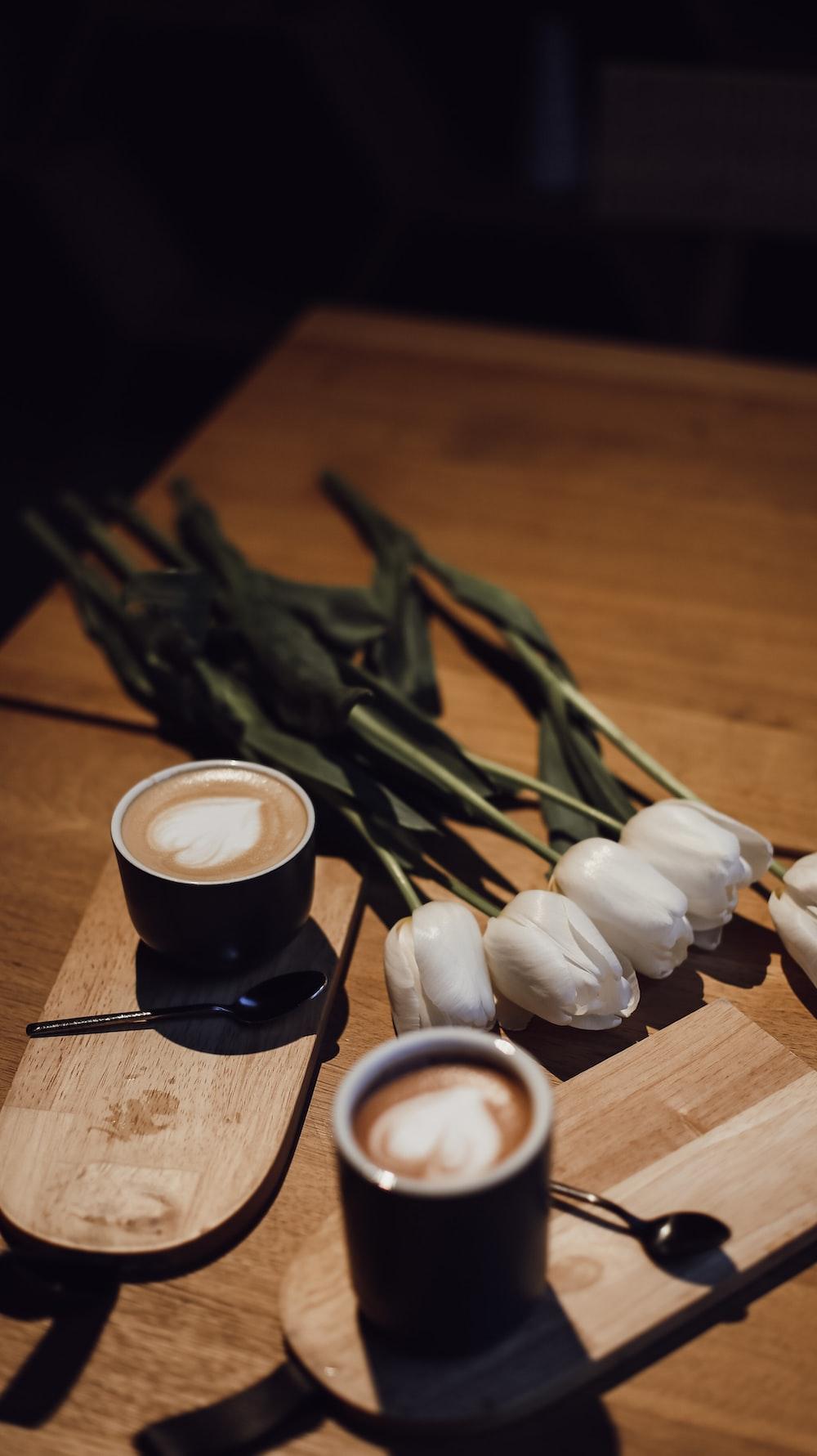 black ceramic mug with coffee beside white garlic and black and white ceramic mug on brown