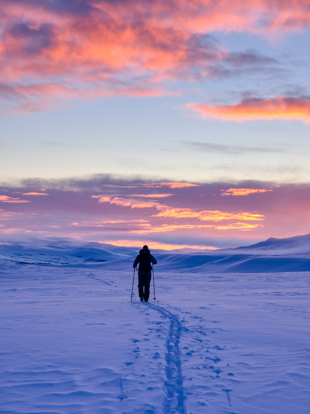 man in black jacket walking on snow covered ground during sunset