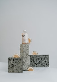 white plastic bottle on brown and gray marble table