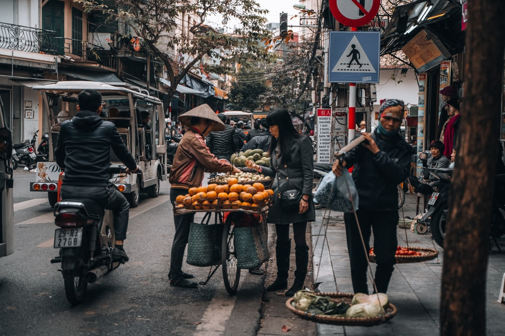 man in black jacket standing near food cart during daytime