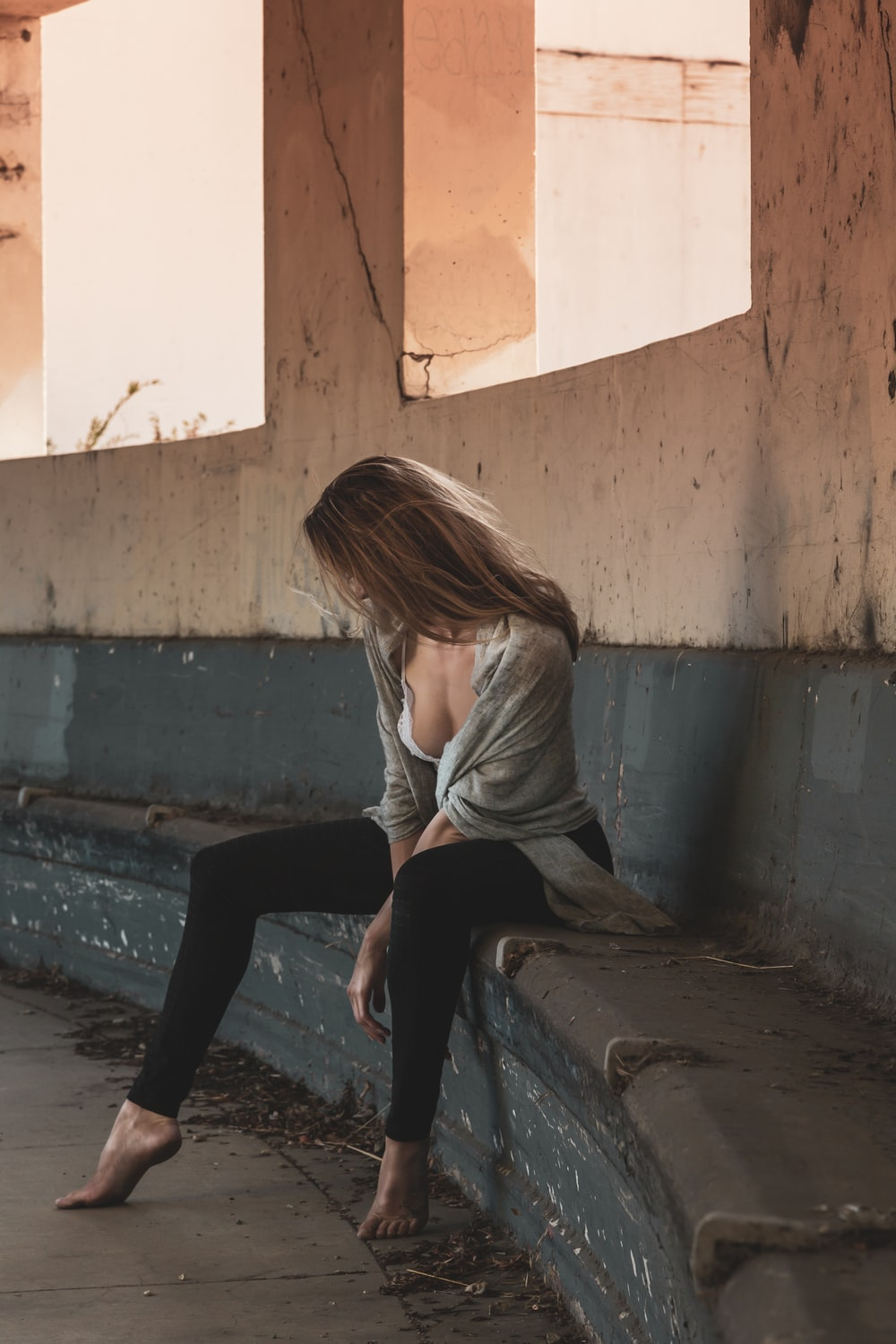woman in gray long sleeve shirt and black pants sitting on concrete bench