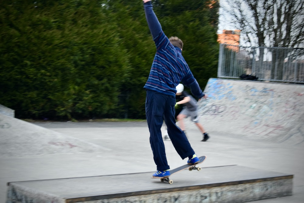 man in blue long sleeve shirt and black pants riding blue and white skateboard during daytime