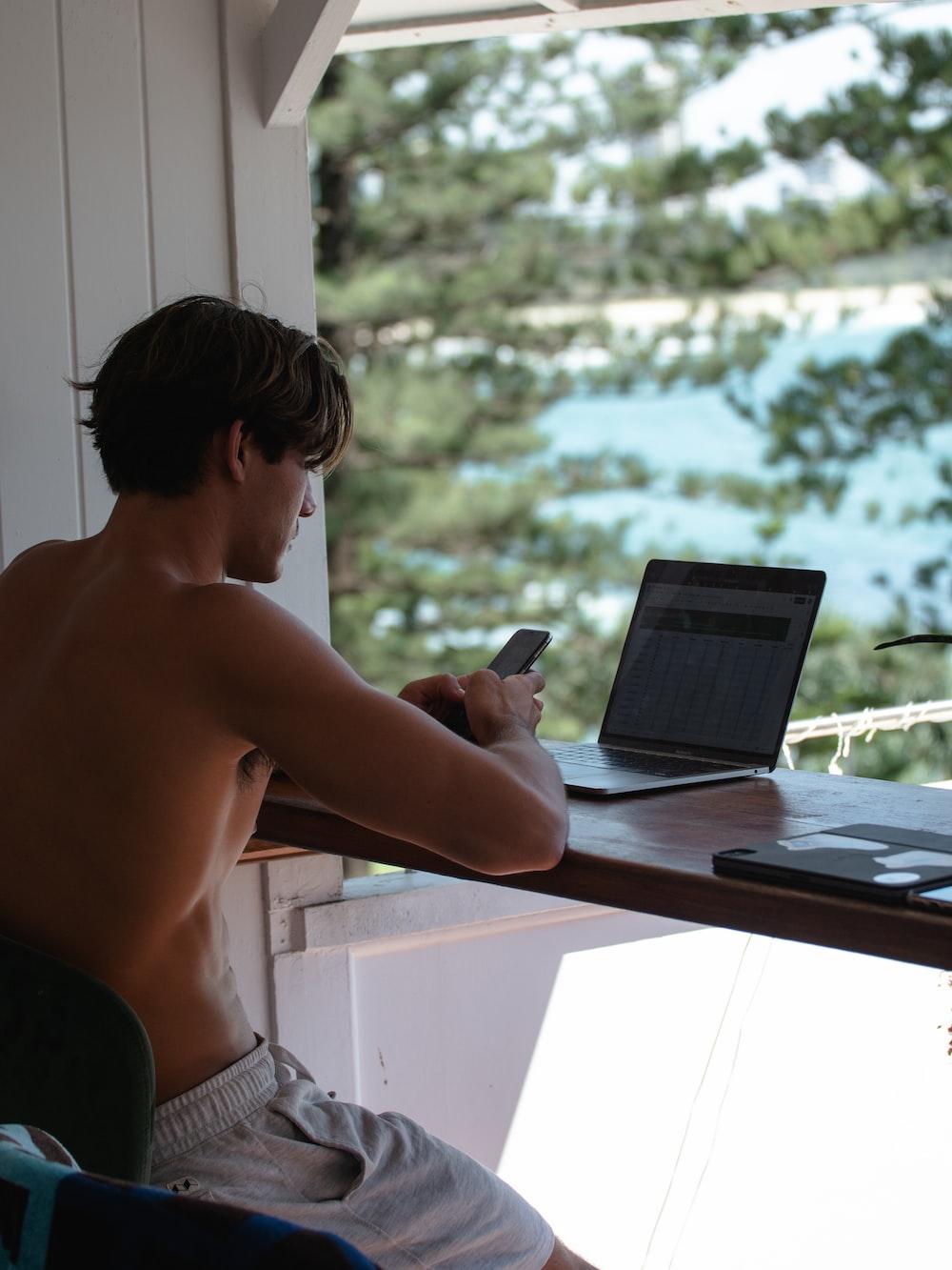 topless man using black laptop computer