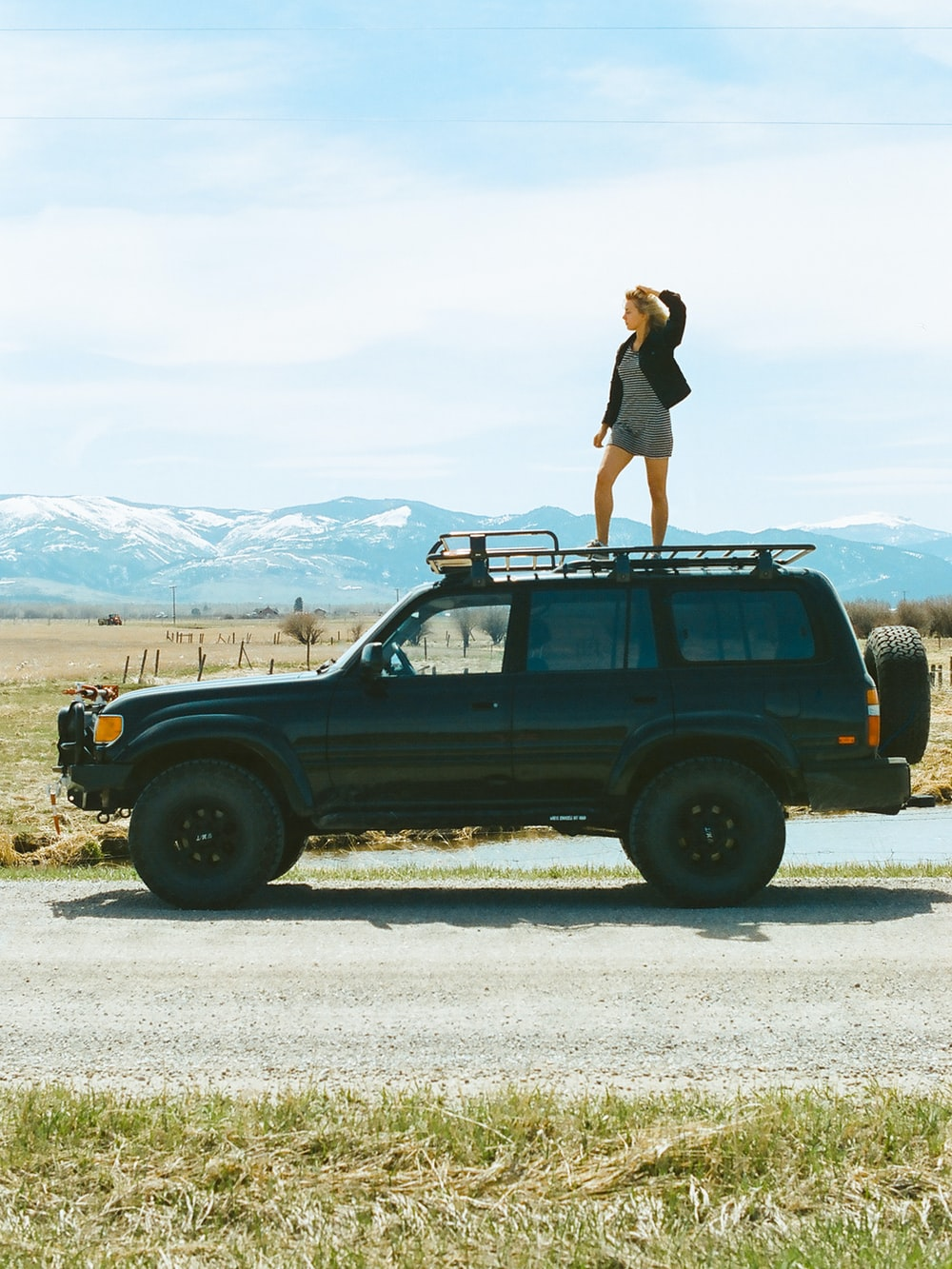 woman in black tank top and black shorts standing on black suv during daytime