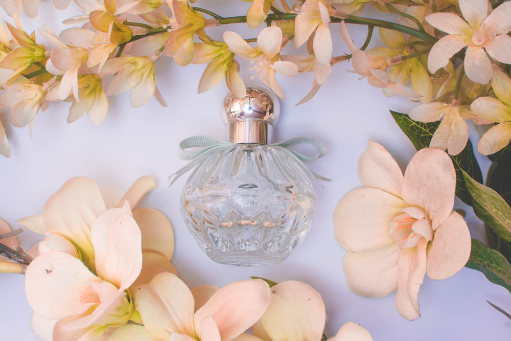 clear glass perfume bottle with white flowers