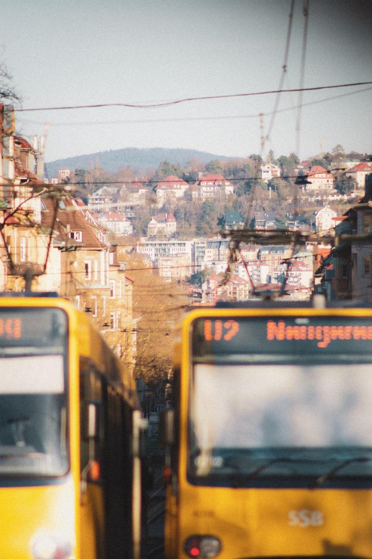 yellow and white train on rail tracks during daytime
