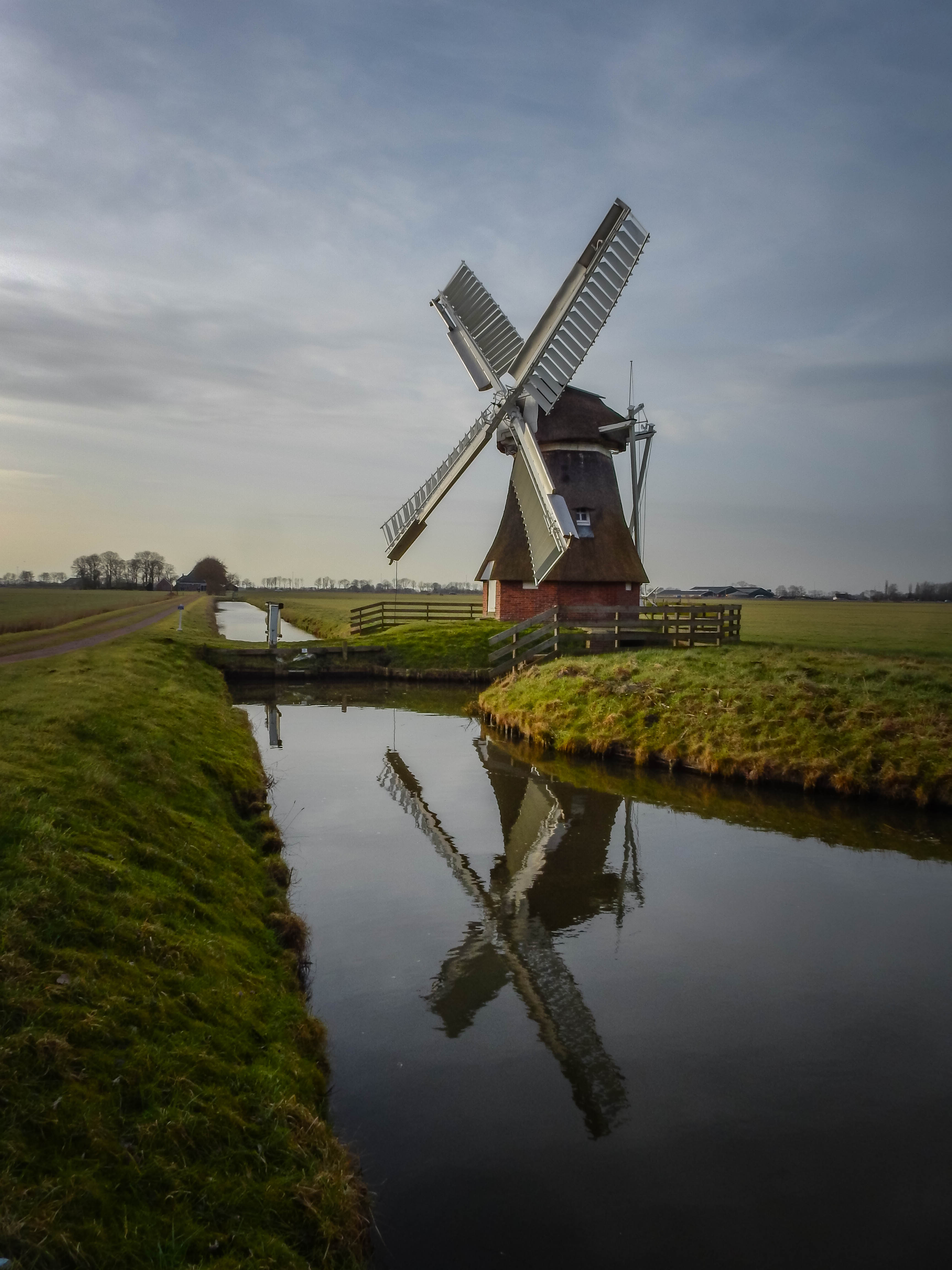 windmill near river under cloudy sky during daytime