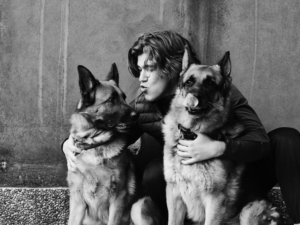 grayscale photo of man and woman with dog