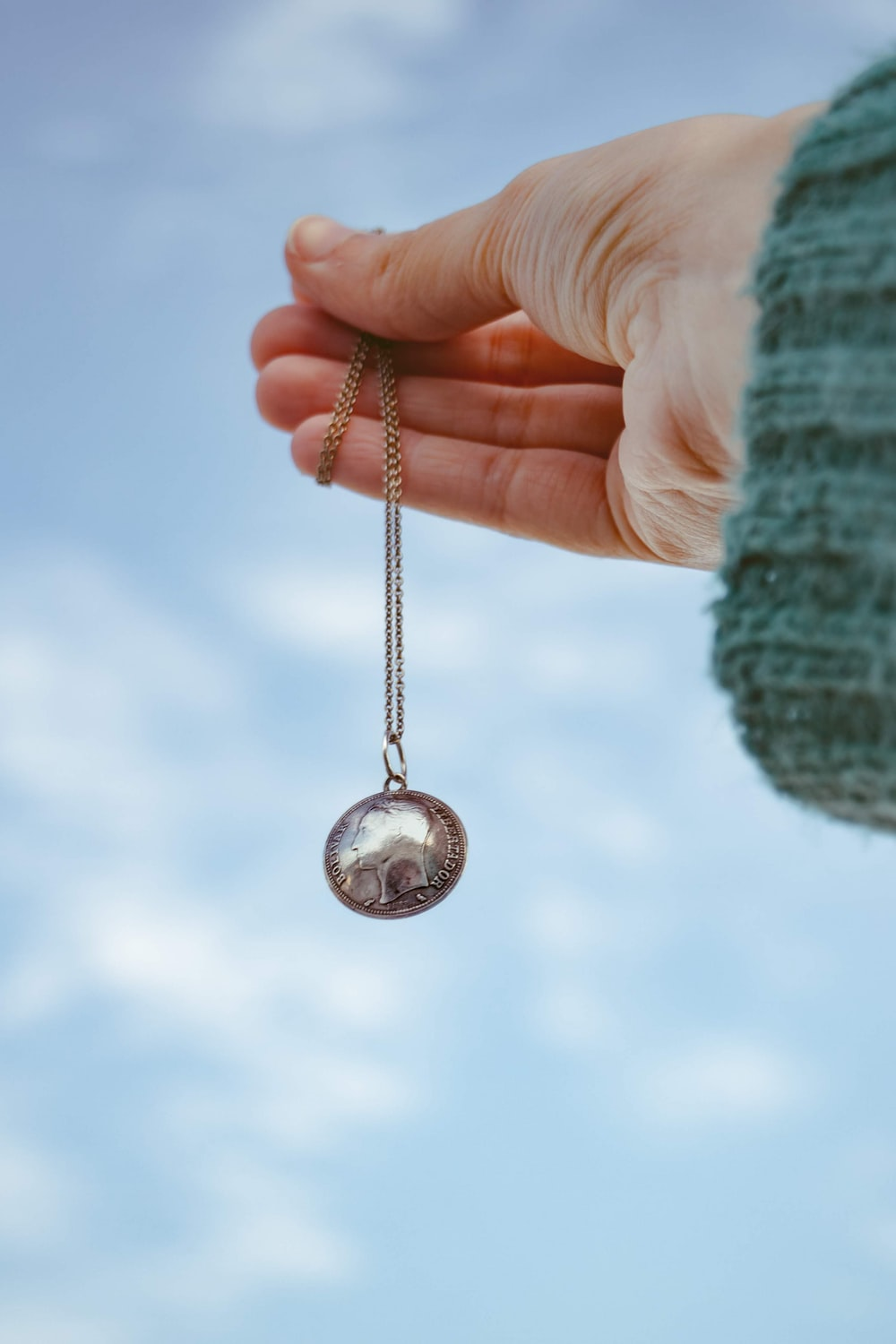 silver round pendant on persons hand