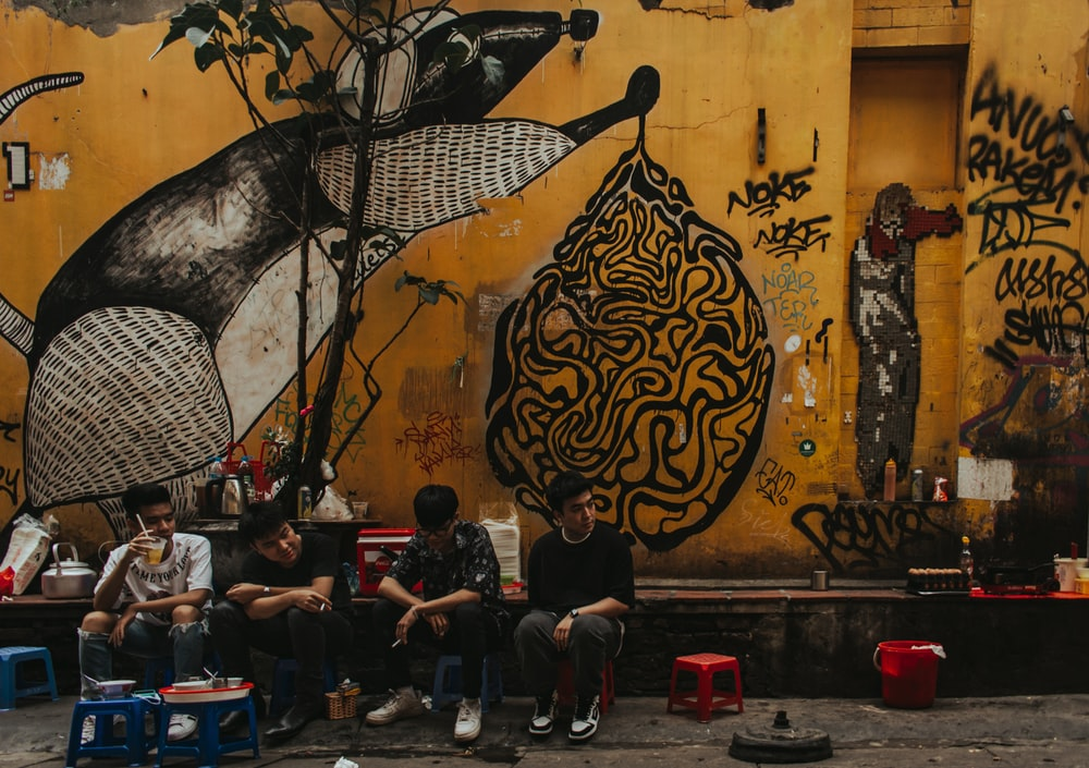 people sitting on chairs near wall with black and white floral painting