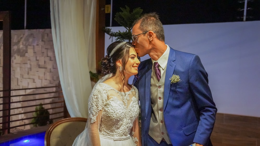 man in blue suit jacket kissing woman in white floral lace wedding dress