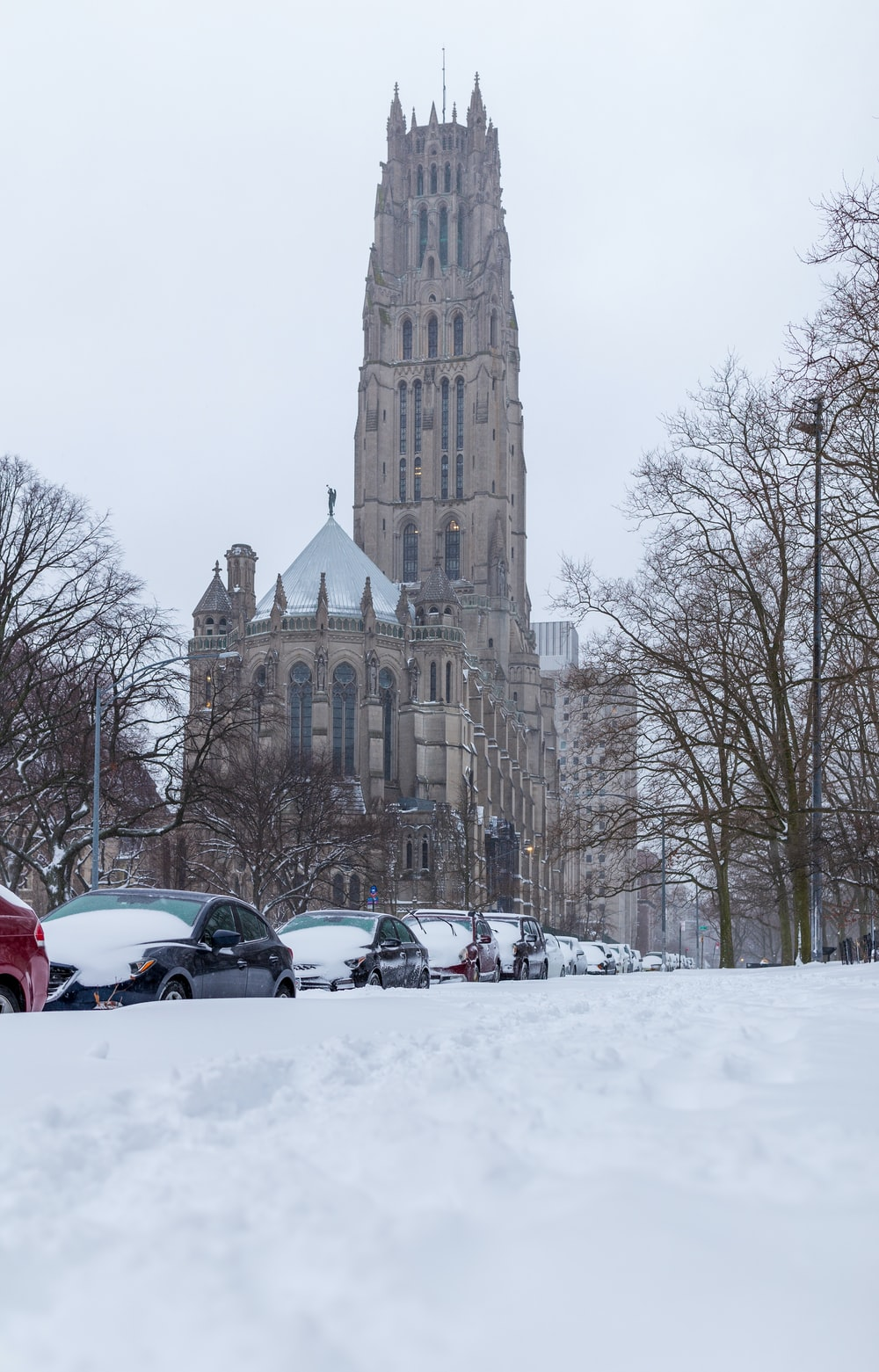 cars parked on snow covered road near brown concrete building during daytime