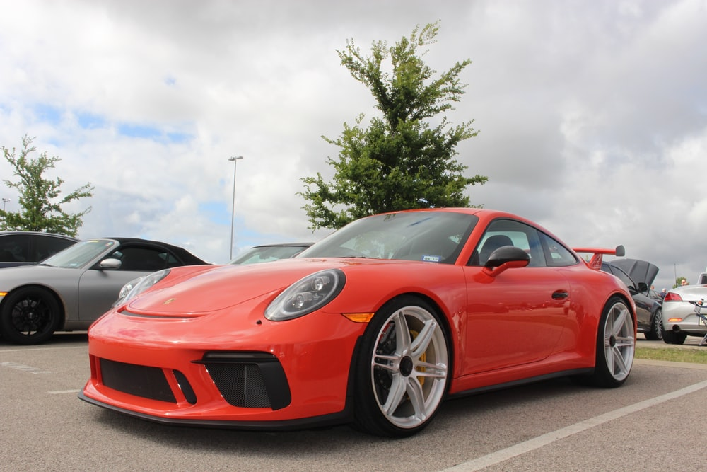 red ferrari 458 italia parked on gray asphalt road during daytime