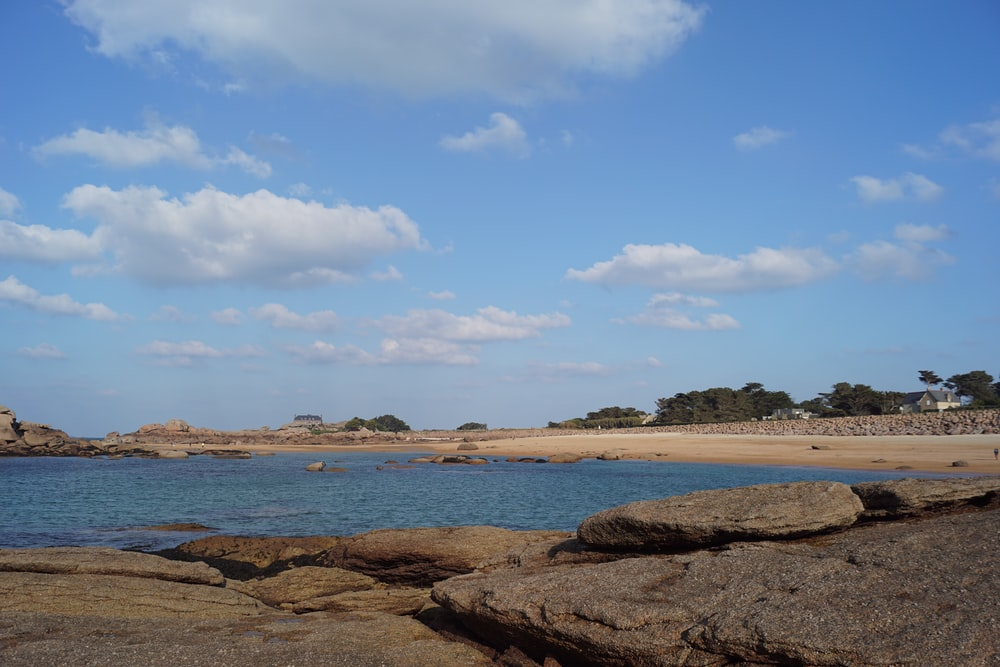 brown rocky shore under blue sky and white clouds during daytime