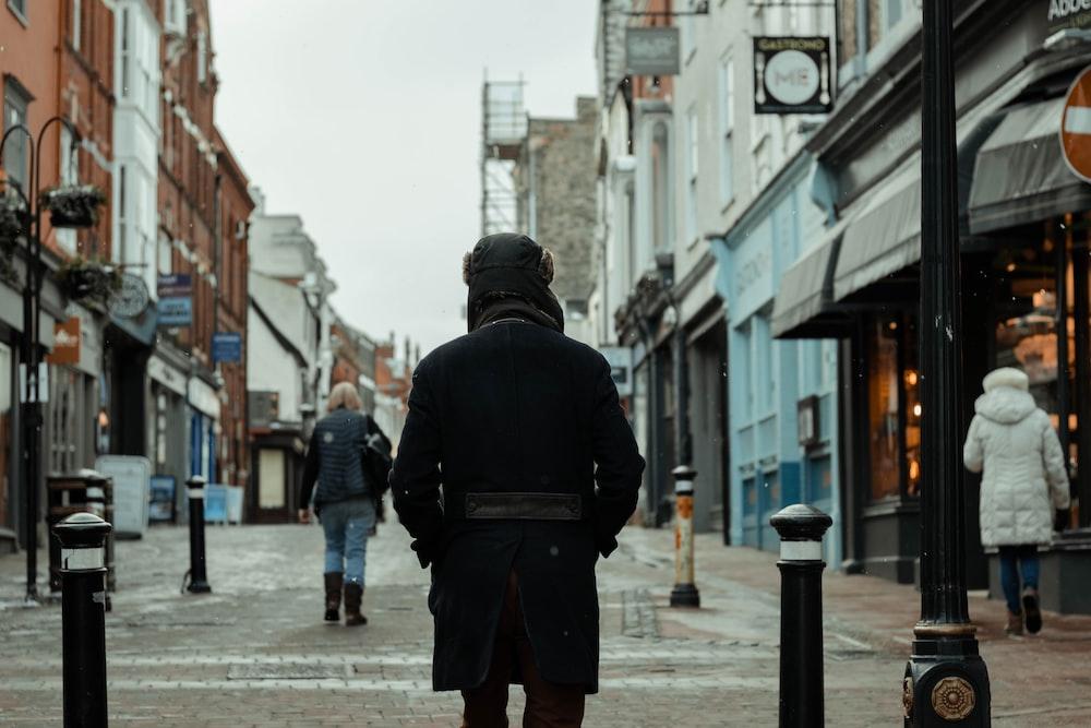 man in black jacket and black backpack walking on street during daytime