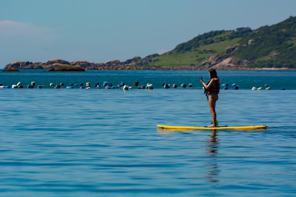 woman in black bikini standing on yellow surfboard on blue sea during daytime