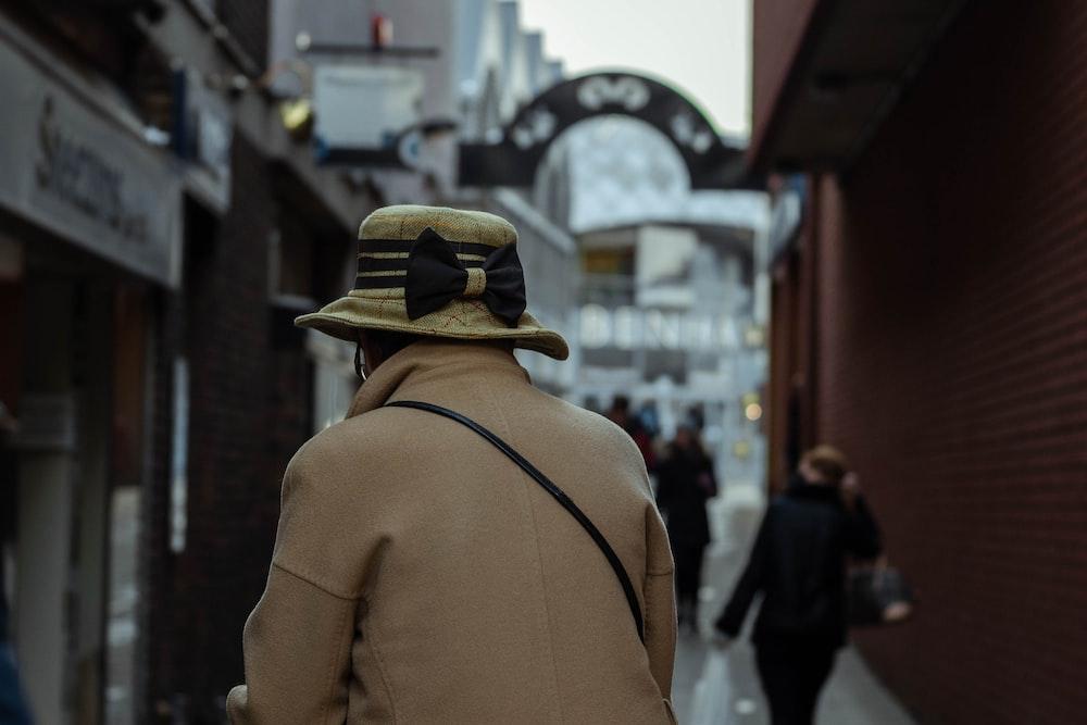 man in brown jacket and black hat walking on street during daytime