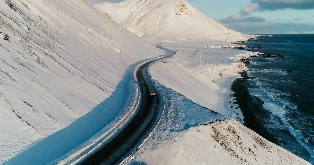 black asphalt road in between snow covered ground during daytime