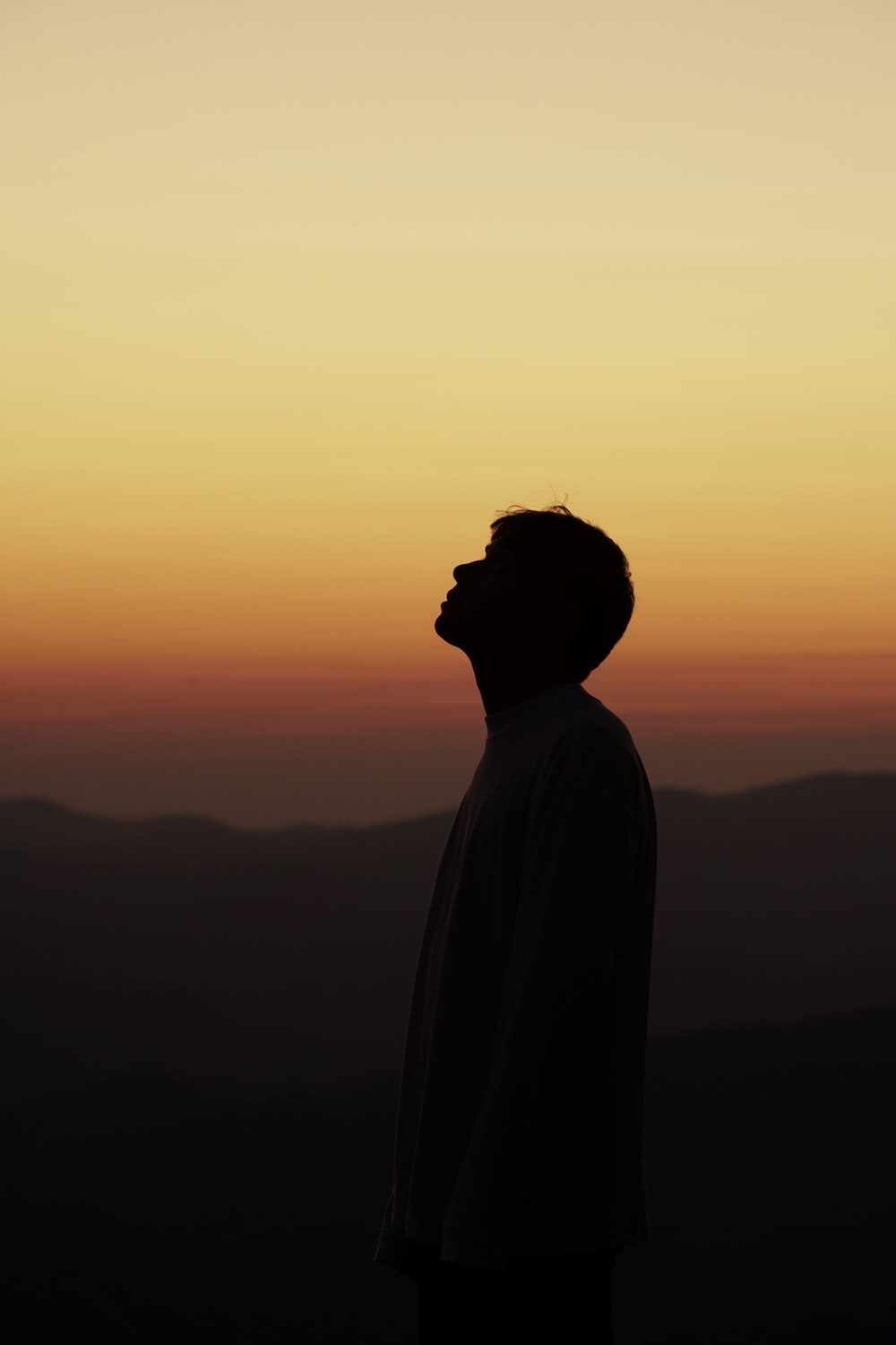 silhouette of person standing during sunset
