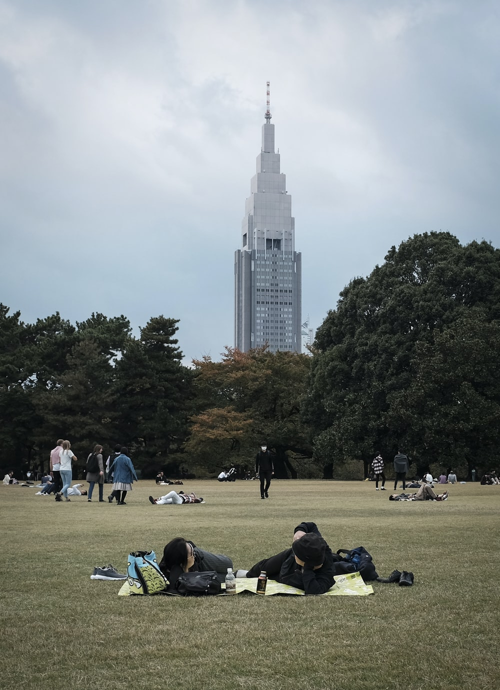 people sitting on green grass field near white high rise building during daytime