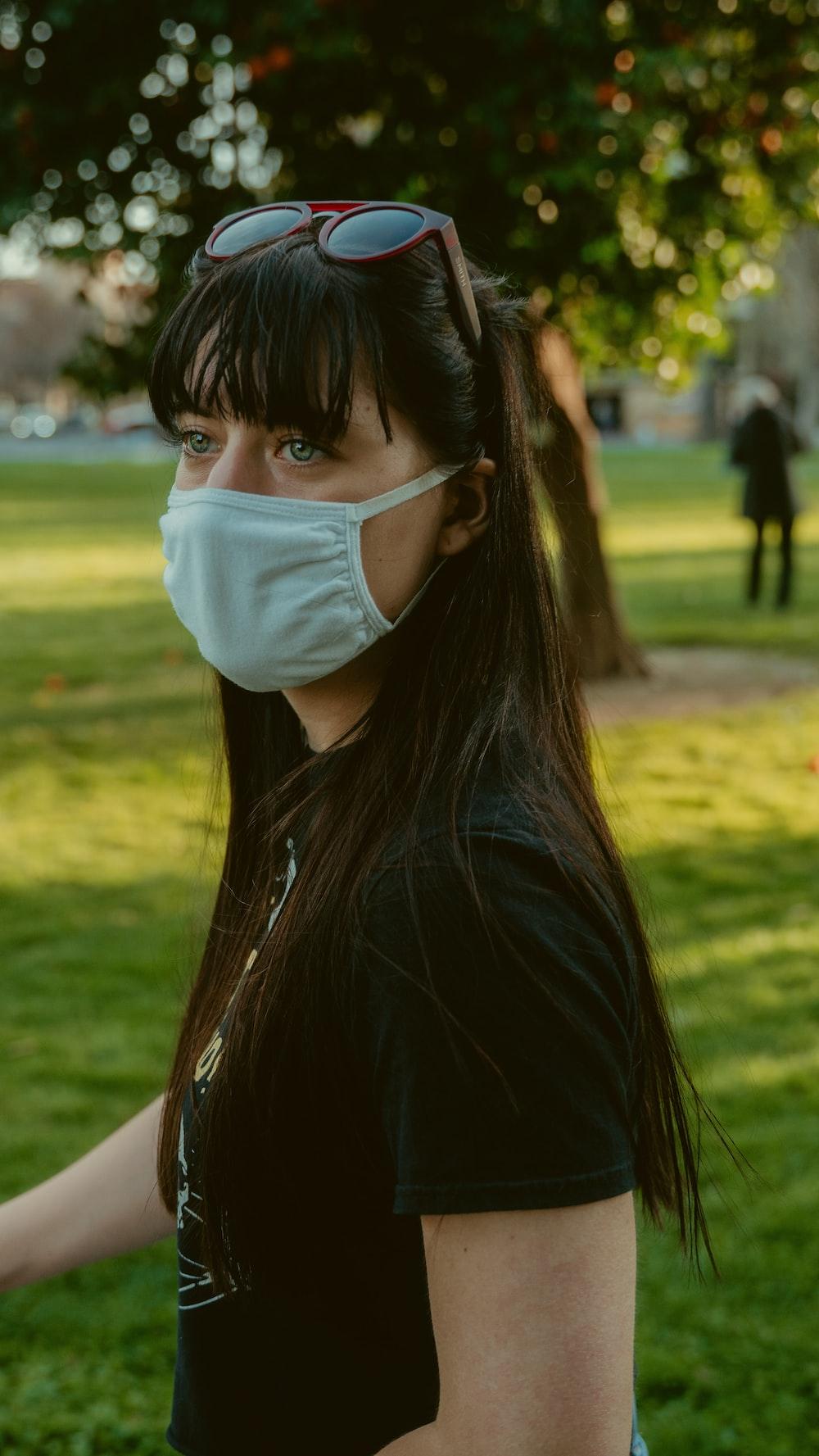 woman in black shirt wearing white face mask