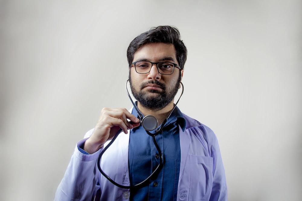 man in blue dress shirt wearing black framed eyeglasses