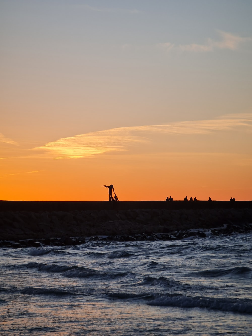 people standing on the beach during sunset