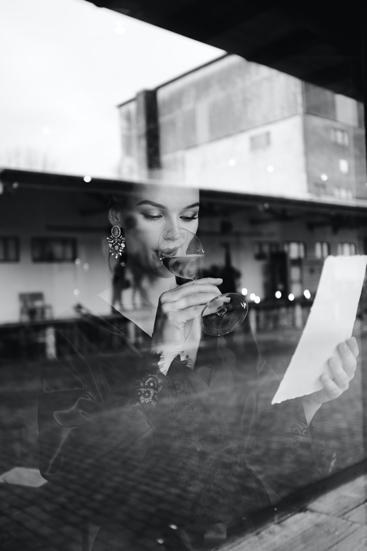 woman in black and white polka dot long sleeve shirt holding white printer paper