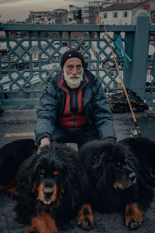 man in black leather jacket sitting beside black long coated dog