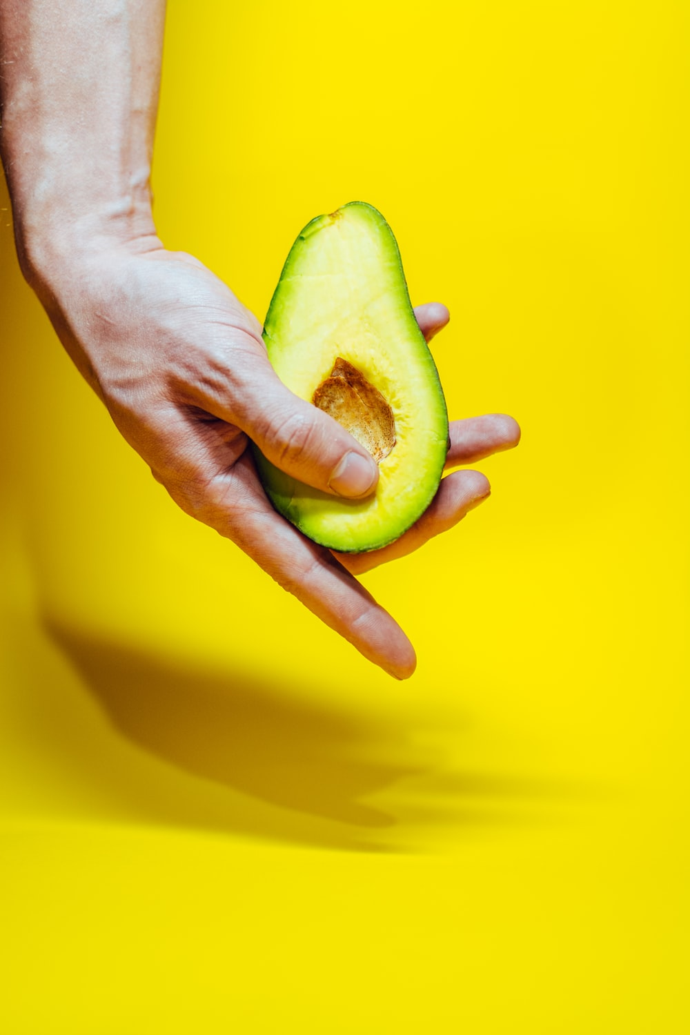 person holding green and yellow fruit