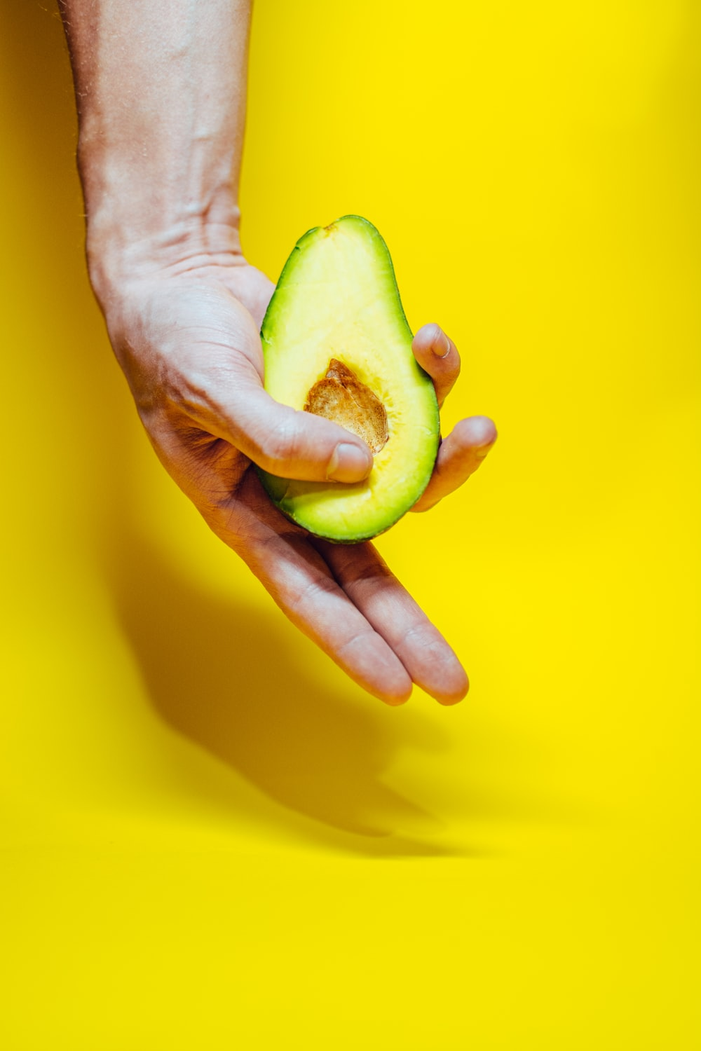 person holding green fruit on yellow surface