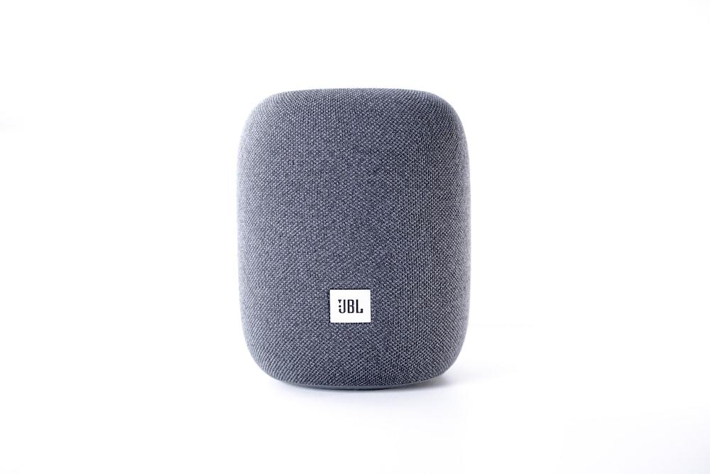 black jbl portable speaker on white surface