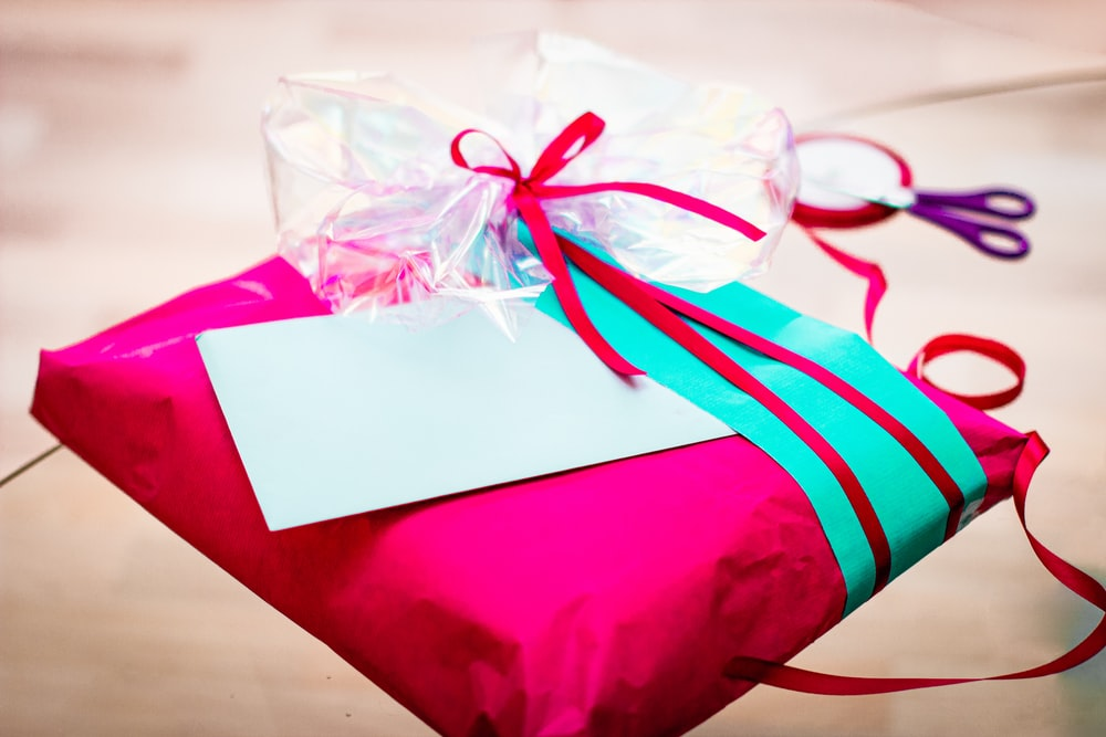 red and white gift box with white ribbon