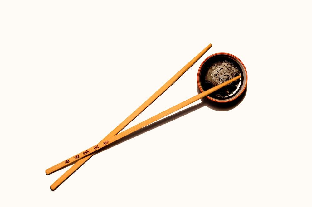 brown wooden chopsticks with black round container