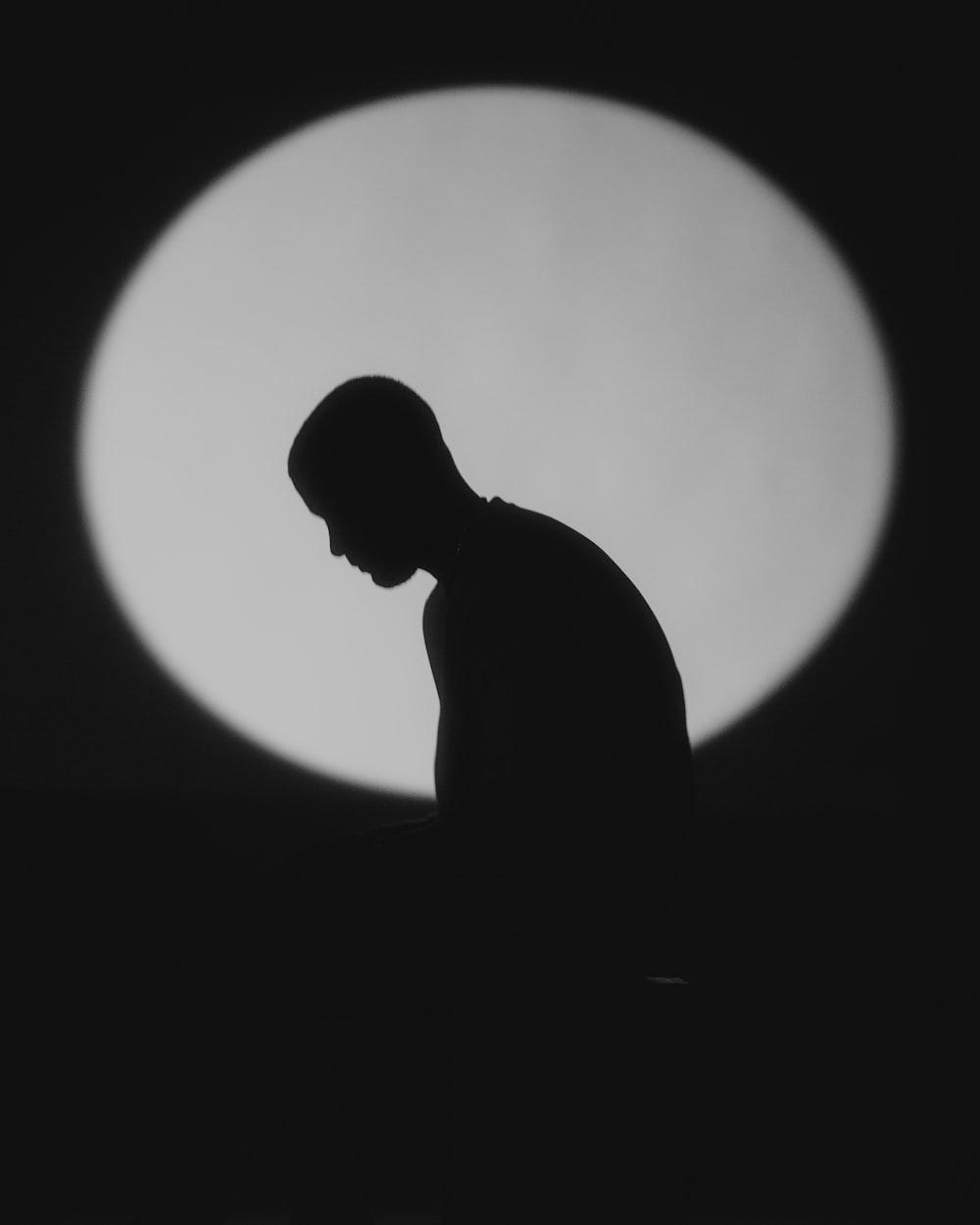 silhouette of man sitting on floor