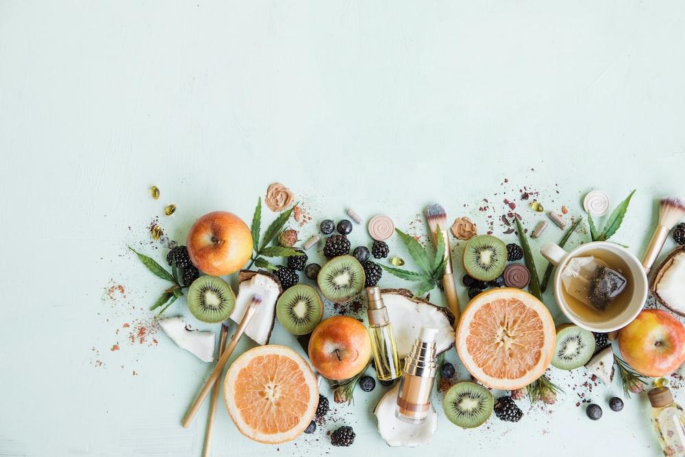 sliced orange fruit and green leaves on white table