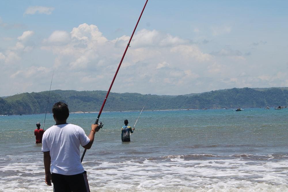 man in white shirt fishing on sea during daytime