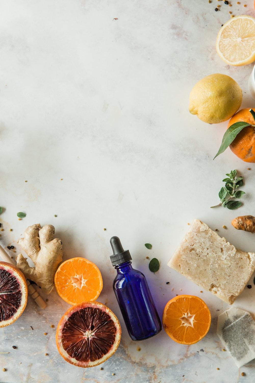 orange fruit beside blue glass bottle