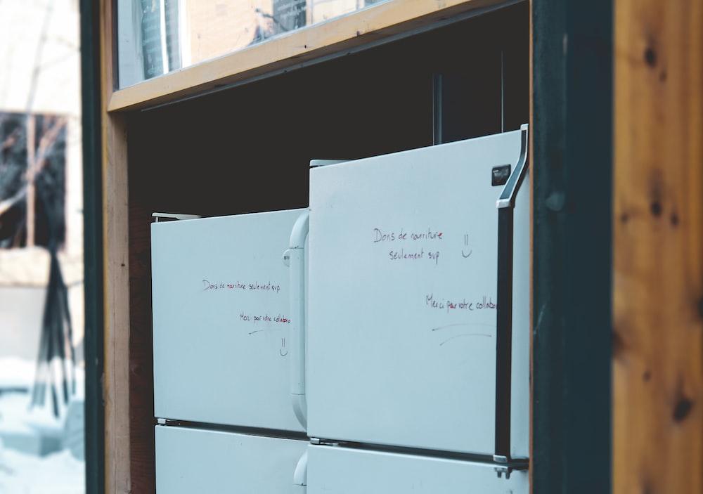 white top mount refrigerator beside brown wooden shelf