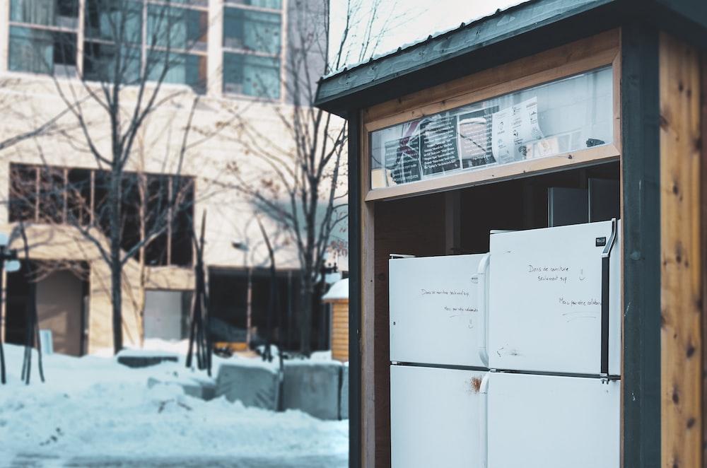 white top mount refrigerator near brown wooden framed glass window