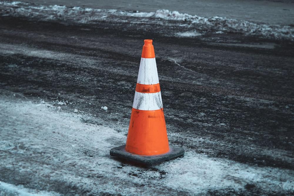 orange and white traffic cone on black sand
