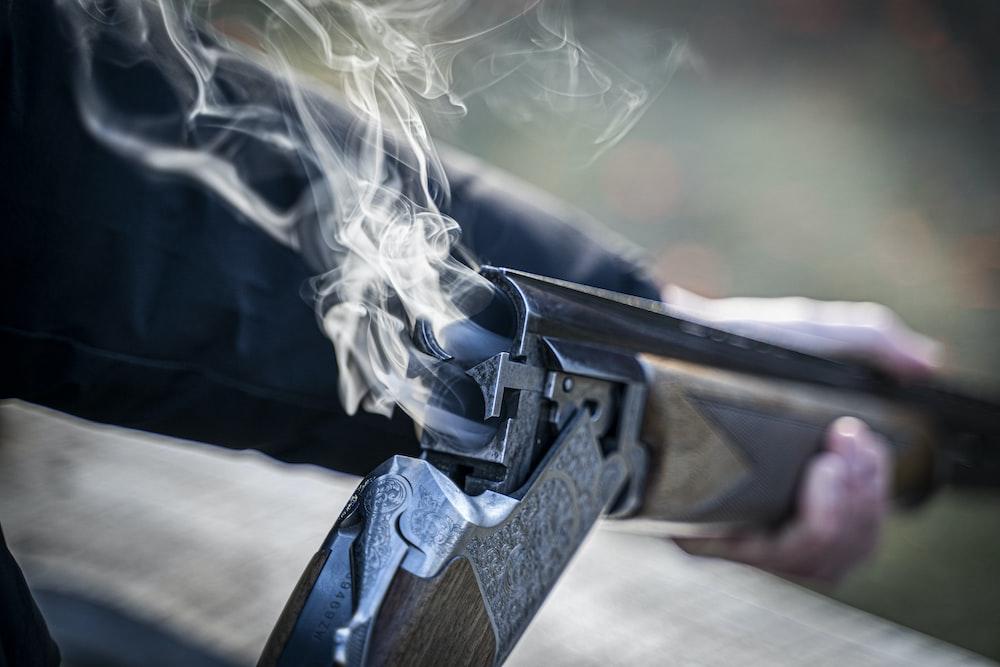black semi automatic pistol with white smoke