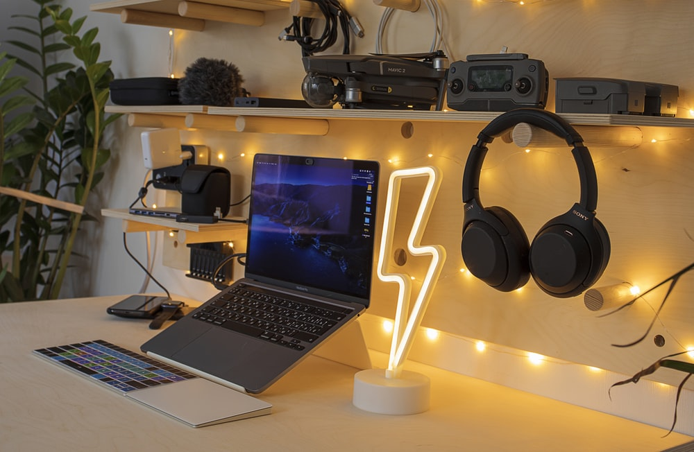 black and silver laptop computer beside black and gray headphones