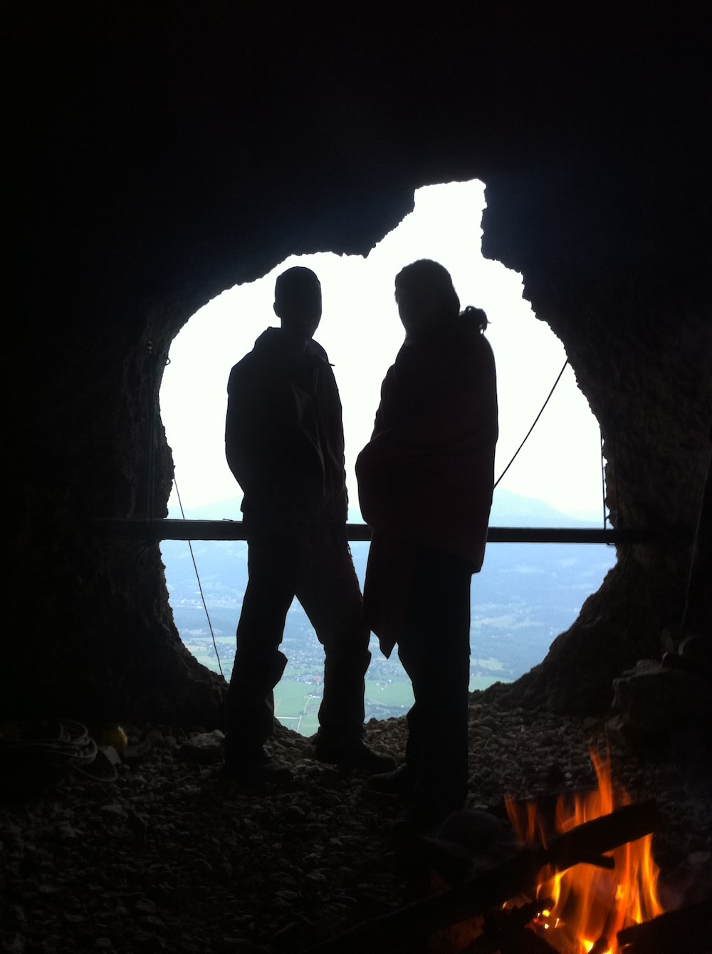 silhouette of man and woman standing in cave during daytime