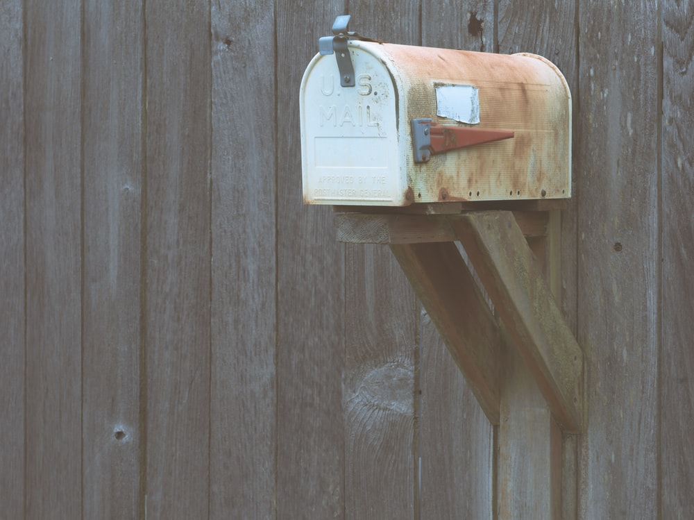 white mail box on brown wooden wall