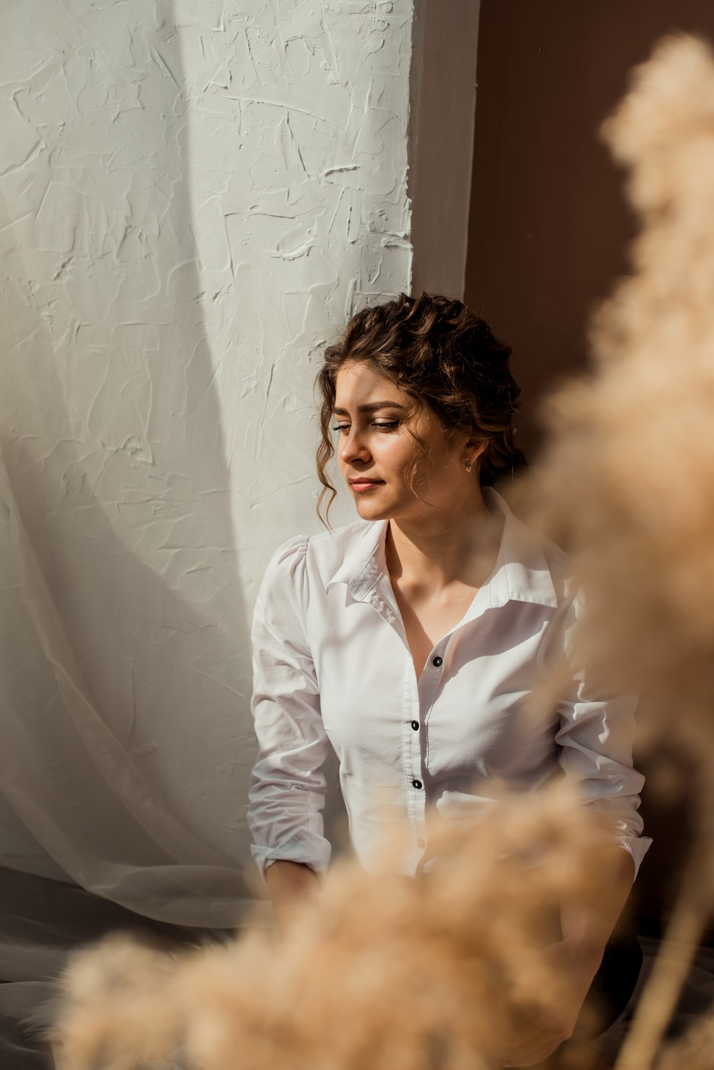 woman in white dress shirt standing beside white wall