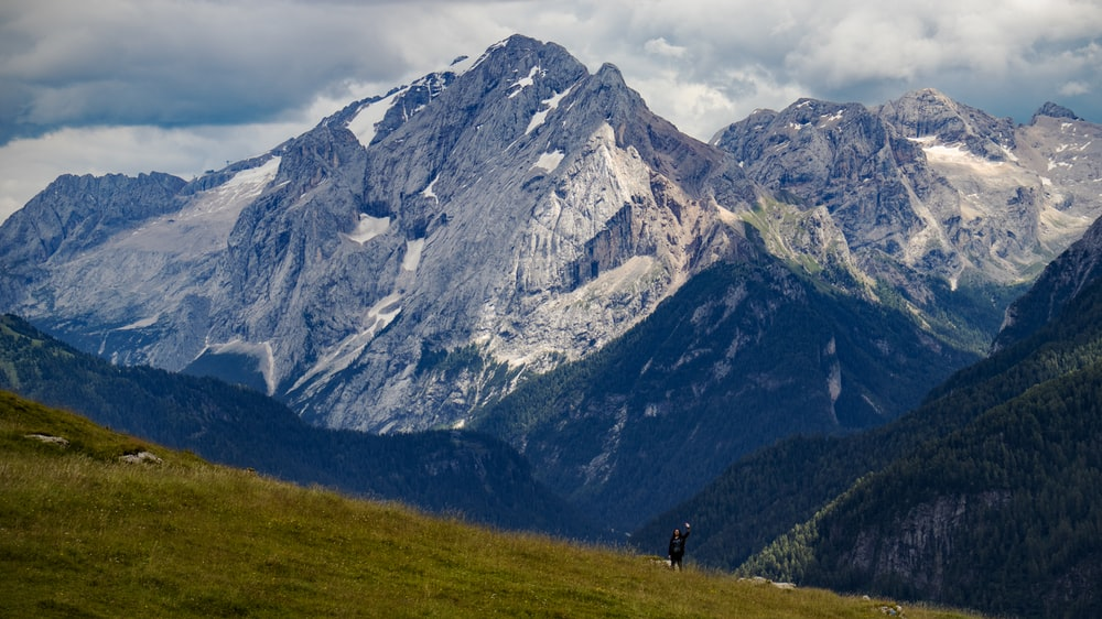 people walking on green grass field near mountain during daytime