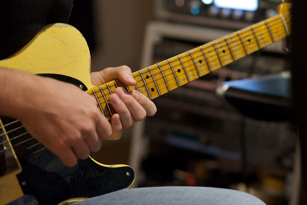 person playing yellow and black acoustic guitar